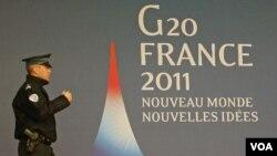 Seorang polisi melintasi logo dan slogan G20 'Dunia Baru, Ide Baru' menyambut pertemuan puncak G20 di Cannes, Perancis (2/11).