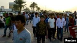 FILE - Migrant workers walk on the Corniche in Doha, Qatar.