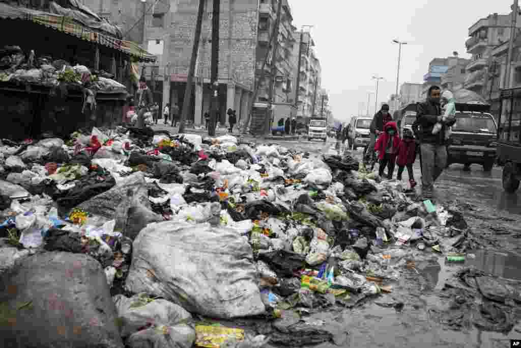 Une famille traversant une rue jonchée d'ordures.