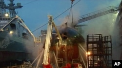 In this video image from Ru-RTR Russian state television channel, firefighters spray water on the Yekaterinburg nuclear submarine in a dock at the Roslyakovo shipyard in the Murmansk region, Russia. A fire that erupted while the Yekaterinburg was in dry-d