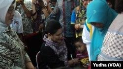 Ibu Negara Iriani Joko Widodo mendampingi anak yang akan diberi imunisasi Polio dalam PIN 2016, Selasa, 8 Maret 2016 (Foto: VOA/Yudha)