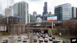 Lalu lintas di jalan raya Interstate 90 sementara kereta commuter Metra melintas di jalur layang di Chicago, 31 Maret 2021.