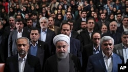 In this photo released by official website of the office of the Iranian Presidency, President Hassan Rouhani, center, Science Minister Mohammad Farhadi, right, and head of the President's office Mohammad Nahavandian, left, listen to the national anthem at the start of a ceremony marking Student Day at Tehran University in Tehran, Iran, Tuesday, Dec. 6, 2016.