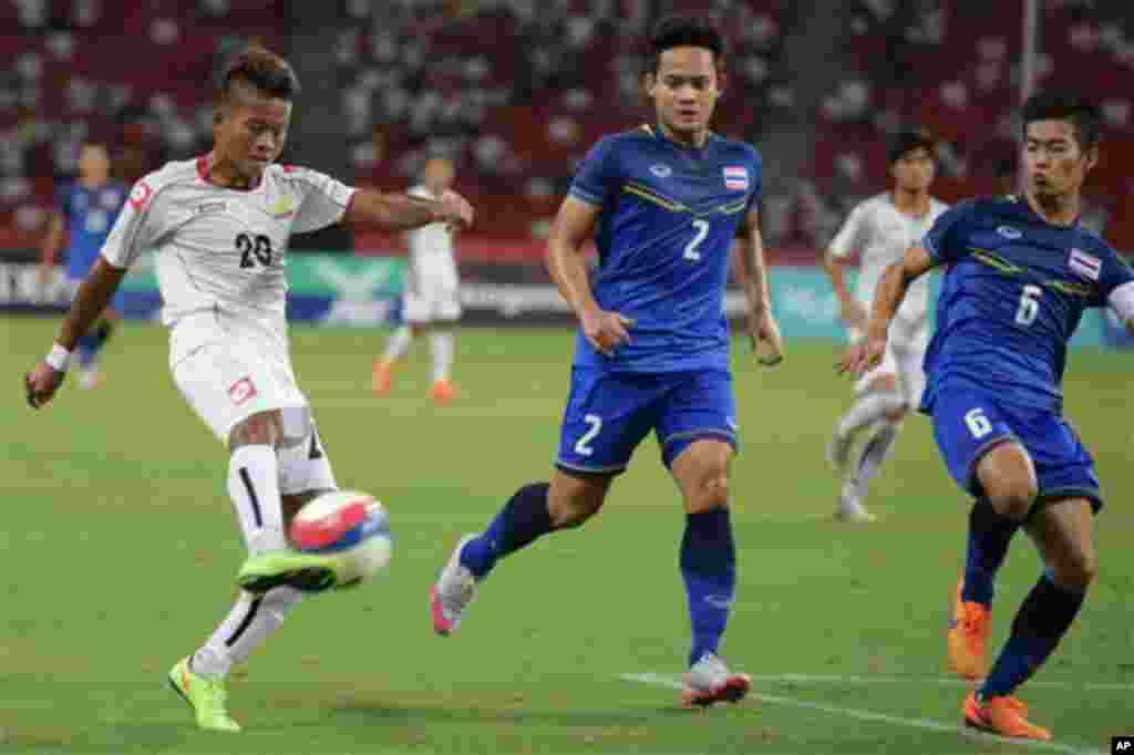 Shine Thura of Myanmar, left, attempts a shot past Peerapat Notechaiya, center, and Sarach Yooyen, right, of Thailand, during the soccer final at the SEA Games in Singapore, Monday, June 15, 2015. (AP Photo/Joseph Nair)