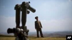 Kolonel Kim Chang Jun dari angkatan bersenjata Korea Utara berdiri di belakang teropong yang diarahkan ke zone demilitarisasi (DMZ) yang memisahkan kedua Korea.