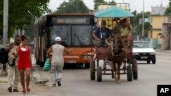 Residentes de La Habana, Cuba, usan un coche tirado por caballos y un autobús el 12 de septiembre de 2019.