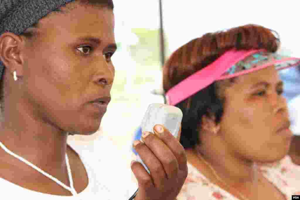 感染了愛滋病毒的傳統治療師維麗斯瓦.馬農杜(左)在非政府組織負責衛生的人士諾姆辛吉斯•霍皮斯的陪伴下,在布隆古拉區對人群講話。 (美國之音達倫.泰勒拍攝)