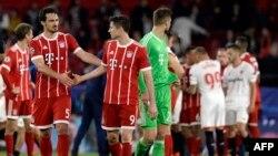 Le défenseur allemand du Bayern Munich Mats Hummels, à gauche, se serre la main avec son coéquipier attaquant Robert Lewandowski à la fin du quart de finale de la Champions League contre le FC Sevilla au stade Ramon Sanchez Pizjuan à Séville, 3 avril 2018