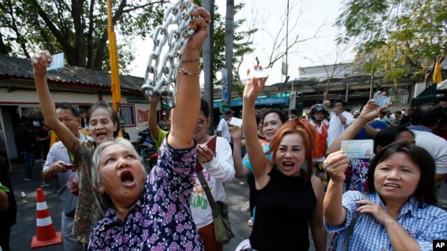 Voters hold their identification cards and the chains that held the gate of the polling station closed, as they demand the right to vote during general elections in Bangkok, Thailand, Feb. 2, 2014.