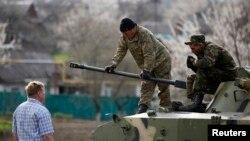 在乌克兰东部,乌克兰士兵站在坦克上与亲俄抗议者交谈(2014年4月16日)