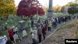 FILE - People line up to visit the grave of women's suffrage leader Susan B. Anthony on U.S. election day at Mount Hope Cemetery in Rochester, New York, Nov. 8, 2016.