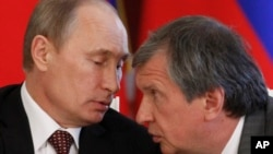 FILE- Russian President Vladimir Putin (L) and CEO of state-controlled Russian oil company Rosneft Igor Sechin speak during a signing ceremony of cooperation agreements with Venezuela, in the Kremlin in Moscow, July 2, 2013.