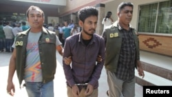 Police officers in Dhaka detain Nahid Hasan, a member of Jamaat-e-Islami, Bangladesh's biggest religion-based party, on suspicion he was involved in Islamic State propaganda, Nov. 25, 2015.
