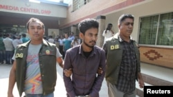 FILE - Police officers in Dhaka detain Nahid Hasan, a member of Jamaat-e-Islami, Bangladesh's biggest religion-based party, on suspicion he was involved in Islamic State propaganda, Nov. 25, 2015.