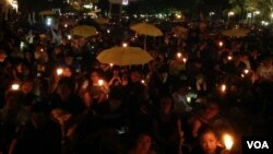 港人在六四烛光晚会上打出象征雨伞运动的黄伞要求真普选