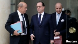 French President Francois Hollande, center, speaks with Defense Minister Jean-Yves Le Drian, left, and Foreign Affairs Minister Laurent Fabius at the end of a defense council at the Elysee Palace in Paris, Jan. 21, 2015.