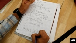 FILE - A student writes notes in the Advanced Placement Physics class at Woodrow Wilson High School in Washington, D.C., February 2014.