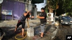 People cool themselves with water in central Baghdad, Iraq, July 16, 2015. The government declared Thursday an official holiday due to scorching temperatures.