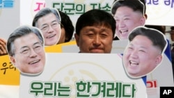 """An activist with cutouts of South Korean President Moon Jae-in, left, and North Korean leader Kim Jong Un participates in a rally welcoming the planned summit between South and North Korea in Seoul, South Korea, April 25, 2018. The signs read: """"We Are A Nation."""""""