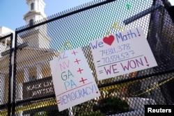 Poster-poster yang menggambarkan hasil pilpres tergantung di luar gereja St. John dekat Gedung Putih setelah mantan wakil presiden Joe Biden diproyeksikan memenangi pilpres, di Washington, Minggu, 8 November 2020. (Foto: Reuters)