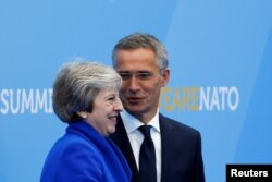 FILE - Britain's Prime Minister Theresa May is welcomed by NATO Secretary-General Jens Stoltenberg at the start of a NATO summit at the Alliance's headquarters in Brussels, Belgium, July 11, 2018.