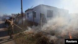 27일 우크라이나 동부 슬로뱐스크 인근 마을의 한 주민이 폭격으로 파괴된 집 주변을 치우고 있다.