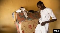 Abdulkadir Abdullahi arranges his school uniform in Maiduguri, Nigeria, October 2016. (C. Oduah/VOA)