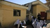 FILE - in this Wednesday, Oct. 7, 2020, students attend an open air class at a primary school in Kabul, Afghanistan, An Afghan education ministry memo banning girls, 12 years old and older, from singing at public school functions, which the education mini