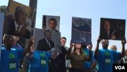 Miembros de la Fundación Metro Industrial Areas muestran fotos de cinco ejecutivos de la industria de fabricación de armas a quienes quieren que el presidente Obama presione por una mayor regulación de las armas de fuego.