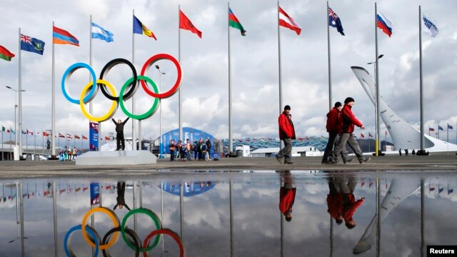 People walk past as the Olympic rings and the cauldron for the Olympic flame are reflected in a puddle of water on the Olympic Park as preparations continue for the Sochi 2014 Winter Olympics, Jan. 30, 2014.