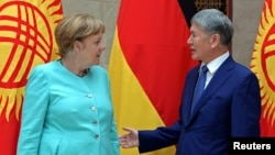 German Chancellor Angela Merkel and Kyrgyz President Almazbek Atambayev talk during their meeting in Bishkek, Kyrgyzstan, July 14, 2016.