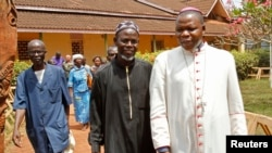 FILE - Archbishop of Bangui Dieudonne Nzapalainga (R) walks with imam Oumar Kobine Layama (2nd R), representative of the local Muslim community, in Bangui Feb. 10, 2014.