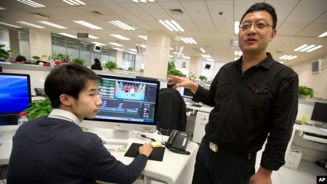 Xinhua All-Media Service deputy director Li Keyong reviews a video editor's animated political cartoon in the organization's updated offices in Beijing, Feb. 24, 2016. Communist Party officials have ordered the catchy mix of click-baiting animation and old-fashioned propaganda.
