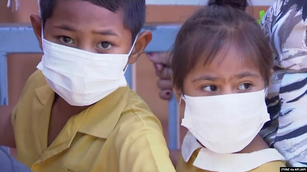 In this November 2019, image from video, masked children wait to get vaccinated against measles at a health clinic in Apia, Samoa.