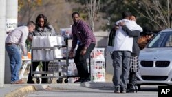 People hug as donations are dropped off at Woodmore Elementary School, Nov. 22, 2016, in Chattanooga, Tenn. A school bus crashed while transporting children home from the school Monday, killing at least six students.