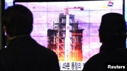 South Koreans watch news report of the Unha rocket launch from Tongchang-ri, North Korea, at Seoul Railway Station, Seoul, Dec. 12, 2012.