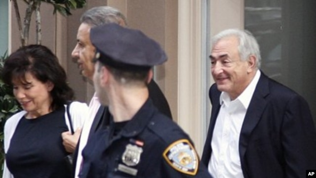 Dominique Strauss-Kahn, right, former head of the IMF leaves his house, accompanied by his wife, Anne Sinclair, left, for the first time after the judge changed the terms of his house arrest, Friday, July 1, 2011 in New York.