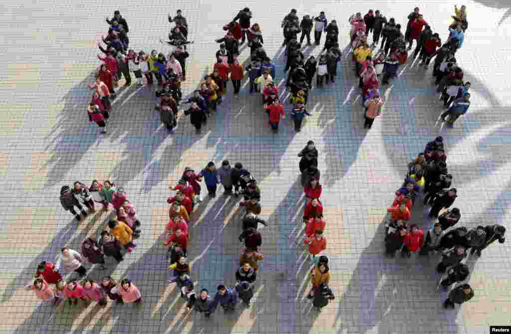 Học sinh đứng tạo hình thành hàng chữ - Happy 2014 - để chào đón năm mới sắp đến tại một trường trung học ở thị trấn Mã An Sơn, tỉnh An Huy, Trung Quốc.