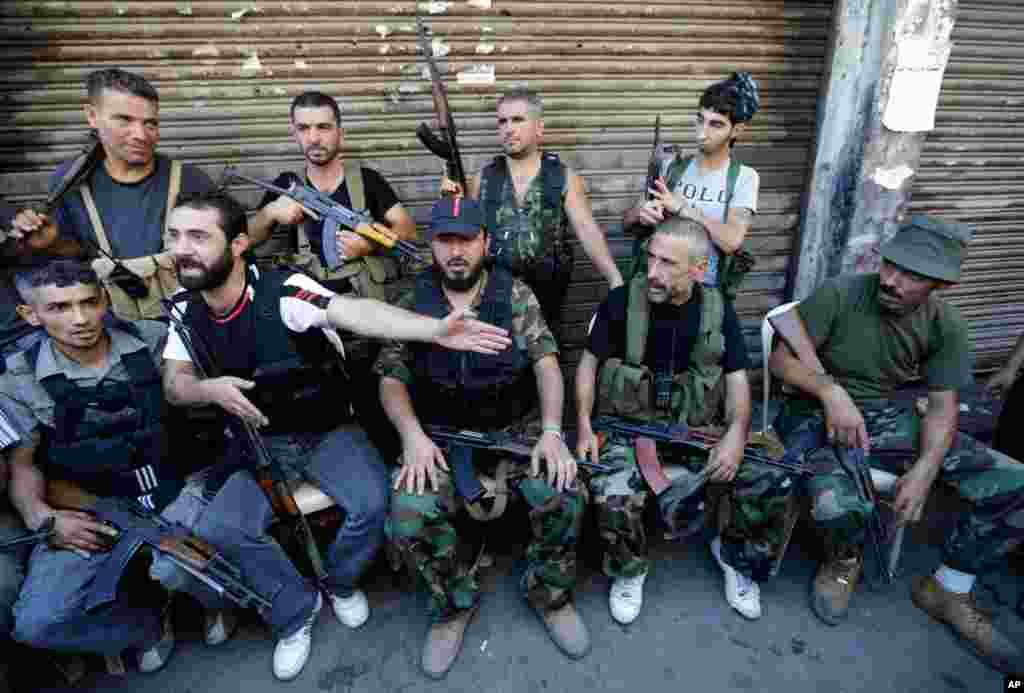 Các tay súng Hồi giáo Sunny ngồi ở một con đường ở Tripoli, Liban nơi đã nổ ra vụ đụng độ giữa nhóm ủng hộ và nhóm chống đối chế độ Syria, 22/8/12