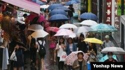 장마전선의 북상으로 전국에 많은 비가 내린 1일 서울 명동에서 시민들이 우산을 쓰고 길을 걷고 있다.