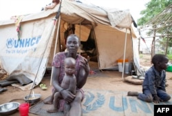 FILE - A woman and her children displaced by fighting in South Sudan sit outside her tent at the Kule camp for Internally Displaced People at the Pagak border crossing in Gambella, Ethiopia, July 10, 2014.