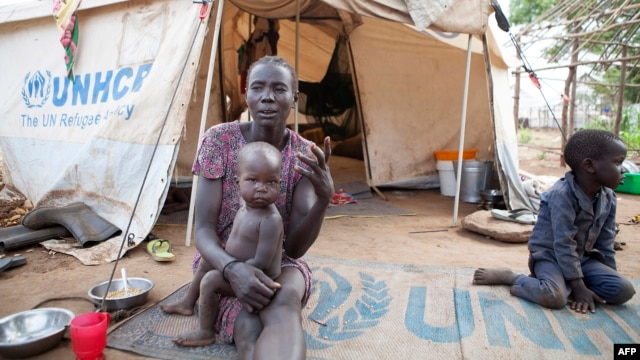 A woman and her children displaced by fighting in South Sudan sit outside their tent at the Kule camp for Internally Displaced People at the Pagak border crossing in Gambella, Ethiopia, July 10, 2014.