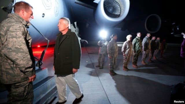U.S. Secretary of Defense Chuck Hagel prepares to step aboard a C-17 military aircraft en route to Kabul, Afghanistan, after greeting U.S. troops (R ) stationed at Manas Air Force Base in Kyrgyzstan, March 8, 2013.