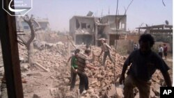 Citizen journalism image provided by Qusair Lens, which has been authenticated based on its contents and other AP reporting, shows Syrians inspecting the rubble of damaged buildings due to government airstrikes, in Qusair, Homs province, Syria, May 18, 201