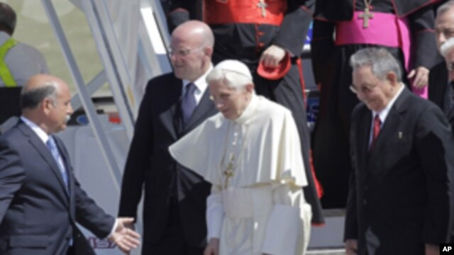 Pope Benedict XVI walks with Cuba's President Raul Castro, second right, as he arrives to Antonio Maceo airport in Santiago de Cuba, Cuba, March 26, 2012.