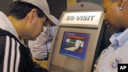 FILE - Department of Homeland Security official (r) assist a passenger (l) as he scans his fingerprint on a machine, part of the exit process at Hartsfield-Jackson Atlanta International Airport in Atlanta. The White House said the country's homeland security agency is immediately altering its electronic visa-free clearance system.