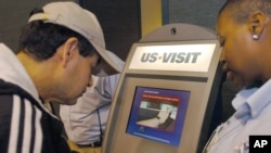FILE - Department of Homeland Security official (r) assist a passenger (l) as he scans his fingerprint on a machine, part of the exit process at Hartsfield-Jackson Atlanta International Airport in Atlanta.