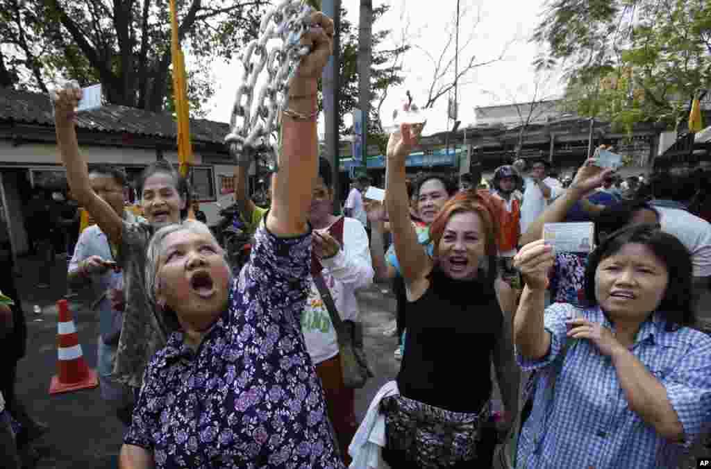 태국에서 조기총선이 치뤄진 2일 방콕의 유권자들이 봉쇄된 투표소 앞에서 신분증을 들고 투표권을 주장하고 있다.