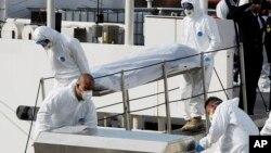 Para anggota penjaga pantai Italia mengangkut jenazah para korban kapal tenggelam di lepas pantai Libya, Senin (20/4).