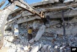 ພາບທີ່ໄດ້ຮັບຈາກກຸ່ມປ້ອງກັນພົນລະເຮືອນໝວກຂາວ (Syrian Civil Defense White Helmets), ທີ່ຖືວ່າເປັນ ກຸ່ມແທ້ຈິງ ແລະພວກລາຍງານຂອງອົງການຂ່າວເອພີ, ສະແດງ ໃຫ້ເຫັນພວກພະນັກງານຂອງກຸ່ມດັ່ງກ່າວ ເຮັດວຽກໃນສະຖານທີ່ເກີດເຫດ, ຊີເຣຍ, 12 ສິງຫາ 2018.